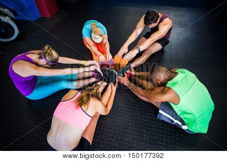 High angle view of friends stretching while sitting in gym