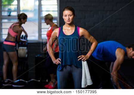 Portrait of fit woman with hands on hip while standing in gym