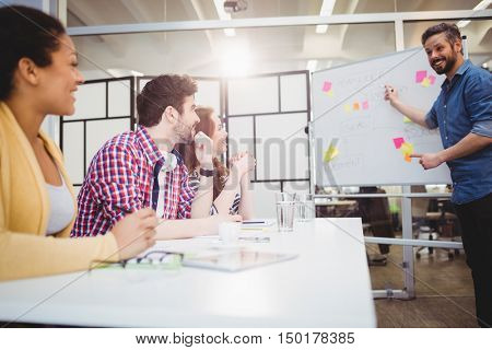 Happy young male executive explaining colleagues at creative office