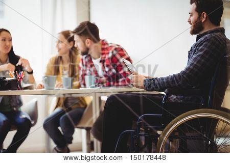 Coworker on wheelchair using digital tablet against photo editors in meeting room at creative office