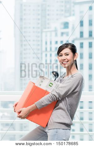 Young asian girl carrying moving box in front of window to city skyline