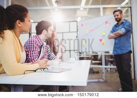Male executive standing in front of colleagues during braintstorming in meeting room at creative office