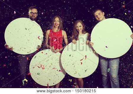 Group of beautiful young people celebrating New Year's Eve holding four blank cardboard circles