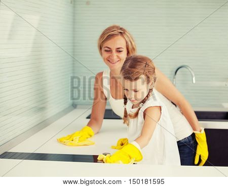 Mother with child washing kitchen. Female with girl cleaning cooker