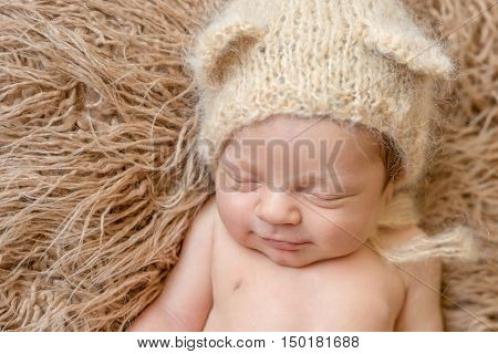asleep smiling newborn baby in knitted hat on furry blanket, close up