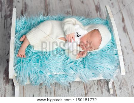 resting newborn baby in white jumper with toy on a little bed with blue furry blanket