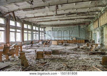 ruined school assembly hall with debris in abandoned Pripyat
