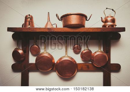 Different kind of vintage copper cookware pans coffee pot and funnel hanging on wooden shelf in kitchen with white rough wall