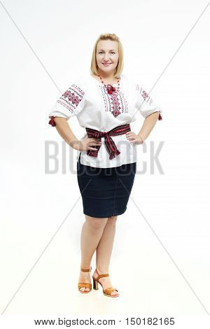 Beautiful Ukrainian plump woman in national costume. Attractive Ukrainian woman wearing in traditional Ukrainian embroidery, standing over isolated white background.