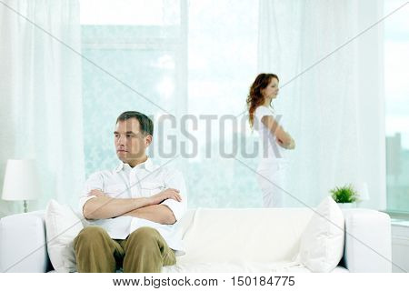 Displeased man sitting on sofa with arms crossed while his wife standing near the window