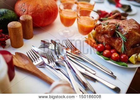 Close-up of silverware on thanksgiving table with roasted chicken