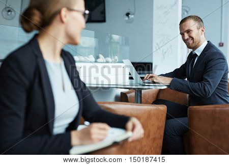 Woman manager making eyes at a young businessman at cafe