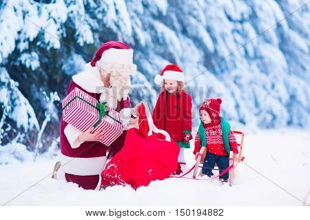 Santa Claus and children opening presents in snowy forest. Kids and father in Santa costume and beard open Christmas gifts. Little girl helping with present sack. Xmas snow and winter fun for family.