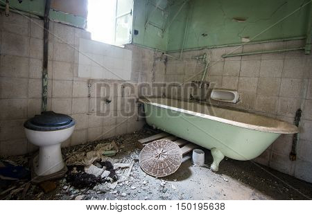 Interior of a dirty empty demolished abandoned bathroom.