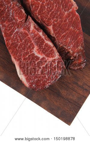 two fresh raw marble beef meat sirloin porterhouse steak on dark wood cut board isolated on white background