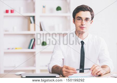 Portrait of handsome young businessman sitting at modern workplace