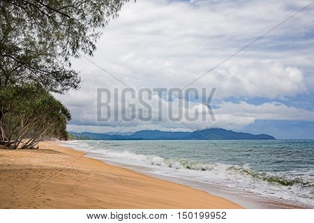 Tropical beach with cloudy sky and waves