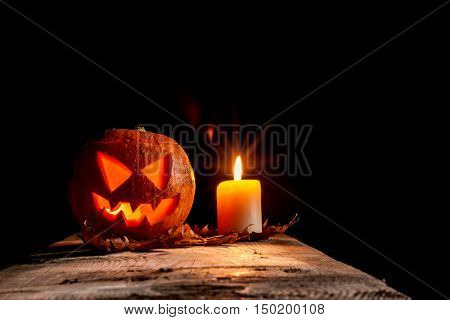 Halloween pumpkin and candle on black background