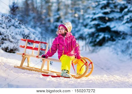 Little girl enjoying sleigh ride. Child sledding. Toddler kid riding a sledge. Children play outdoors. Kids sled in snowy park in winter. Outdoor fun for family Christmas vacation. Fir trees and snow.