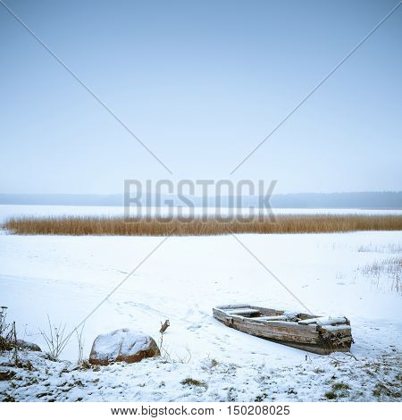 Winter Landscape. Abandoned Frozen Boat on a Lake Covered with Snow. Serenity and Tranquility Concept. Cold Toned Square with Copy Space.