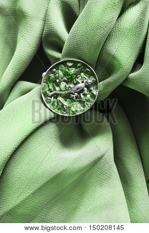 Emerald brooch with silver lizard on crumpled green silk as a background