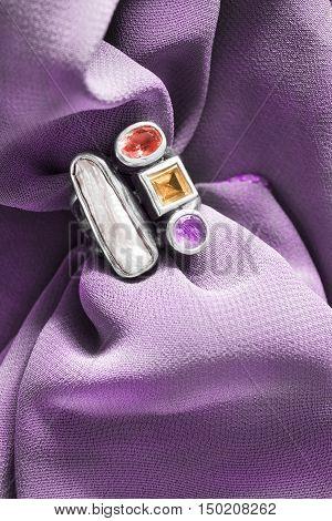 Vintage nacre and gems ring on purple draped silk