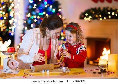 Mother and little girl baking Christmas pastry. Children bake gingerbread. Toddler child preparing cookie for family dinner on Xmas eve. Decorated kitchen or dining room with fireplace tree candles.