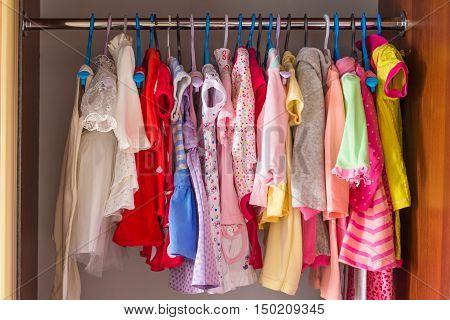 Bright colored children's clothes in the closet