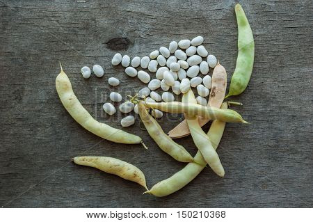 The pods of beans and white beans on a wooden background.