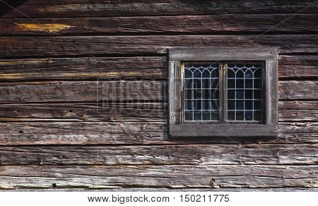 Elegant paned windows at a wooden, timber wall. Powerful timber, log construction in closeup.
