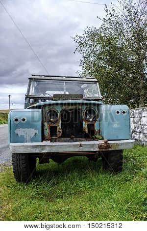 Old rusting abandoned vehicle with peeling paint at the roadside with concrete block on bonnet hood