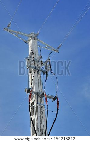 Power pole with external electric separator against the blue sky