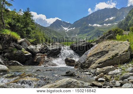 Scene with mountain stream in summer season. Small cascade on mountain river in Carpathian Mountains