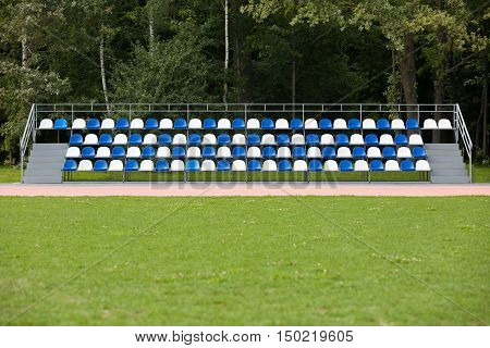 Empty blue and white seats in a footbal or soccer stadium. Grass field and plastic chairs open door sports arena.