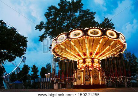 Children's beautiful amusement in entertainment park in the blue hour enabled illumination yellow color against the blue sky