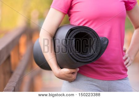 close up of woman's hands holding yoga mat. Girl going to exercise outdoors. Fitness and healthy lifestyle concept