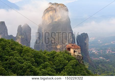 Meteora monasteries. Beautiful view on the Holy Monastery of Roussanov placed on the edge of high rock covered of the morning clouds and mist at sunrise Kastraki Greece