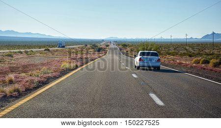 White car on highway in Nevada desert