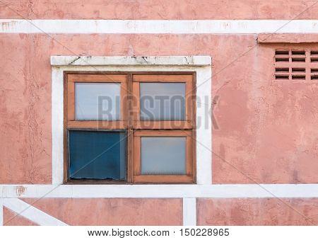Broken wooden window of the obsolete building in the urban area.