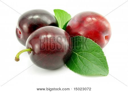 plum fruits with green leafs isolated on white background