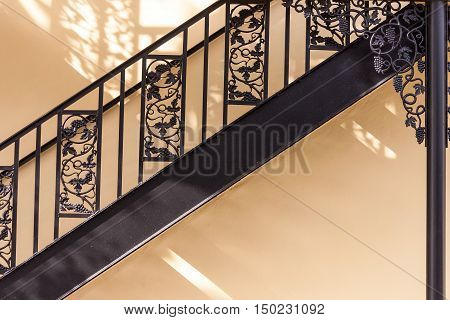 Wrought iron railing detail against yellow wall