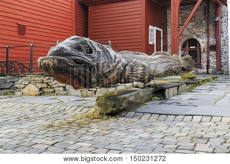 BERGEN, NORWAY - JULY 2, 2016: It is a wooden monument cod installed inside the historic Bryggen.