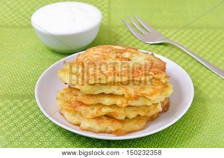 Fried courgette pancakes on the white plate