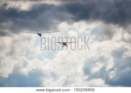 Towplane with a sailglider makeing their way into the cloudy sky