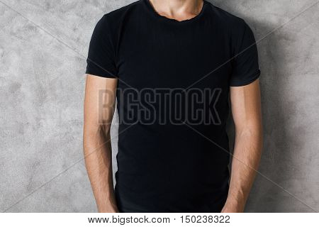 Closeup of young guy's body in empty black t-shirt on textured concrete wall background. Mock up