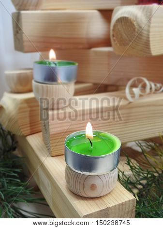Small candles located on several wooden boards.