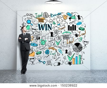 Young businessman in concrete room leaning on whiteboard with business sketch. Success concept