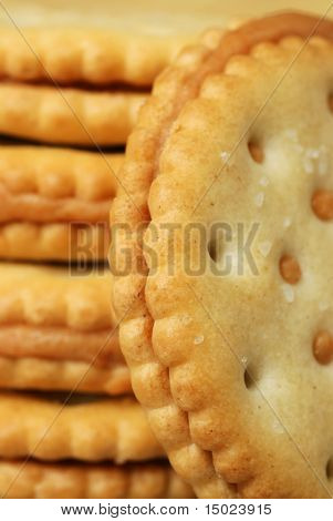 Extreme close-up of peanut butter sandwich cracker standing on edge with additional crackers out of focus in the background.  Abstract with shallow dof.