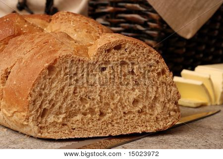 Bread and Butter.  Close-up of sliced, 9-grain, Italian Bread with knife on ceramic cutting board.  Bread basket and sliced butter in soft focus in the background.