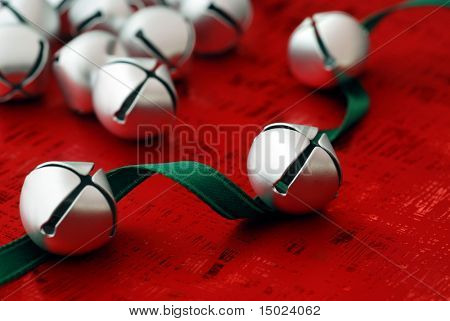 Tiny silver jingle bells with green satin ribbon on shiny red wrapping paper.   Macro with shallow dof